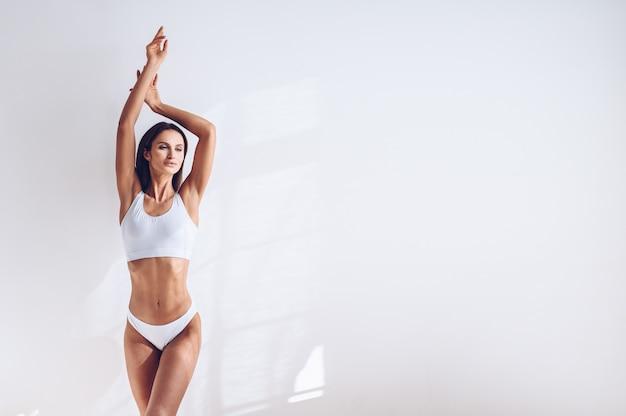 Jonge geschikte vrouw in witte lingerie op witte geïsoleerde muur. gespierde slanke aantrekkelijke vrouw met platte buik. kopieer ruimte voor tekst. lichaamsverzorging, gezond en sportief leven, ontharing, yoga concept