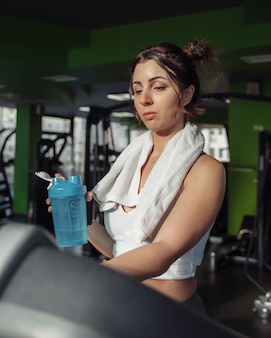 Jonge geschikte vrouw met een handdoek op haar schouders die waterfles op een tredmolen houden. gewichtsverlies concept, aërobe training