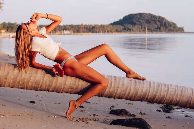 Jonge geschikte vrouw met watermeloen op tropisch strand bij zonsondergang