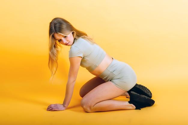 Jonge geschikte vrouw opleiding in sportuitrusting, studiofoto