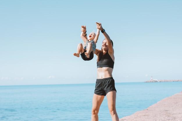 Jonge geschikte vrouwenmamma met weinig leuk meisje die op strand samen uitoefenen