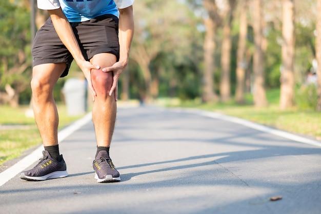 Jonge geschiktheidsmens die zijn verwonding van het sportenbeen houden. spierpijn tijdens training
