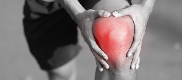 Jonge geschiktheidsmens die zijn verwonding van het sportenbeen houden