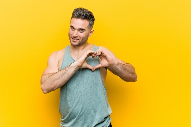 Jonge geschiktheidsmens tegen een gele achtergrond die en een hartvorm met handen glimlacht toont.