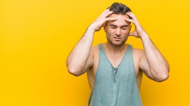 Jonge geschiktheidsmens tegen een gele muur wat betreft tempels en het hebben van hoofdpijn.