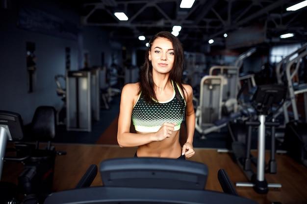Jonge geschiktheidsvrouw die cardiooefeningen doet bij de gymnastiek die op een tredmolen loopt.
