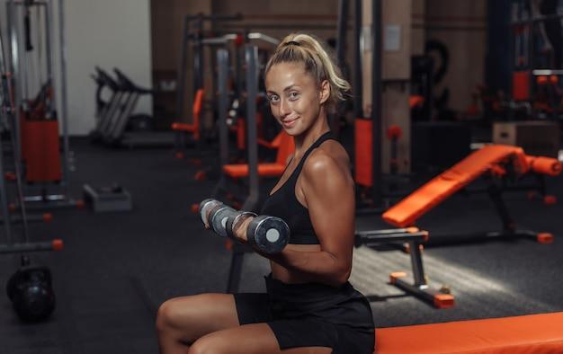 Jonge geschiktheidsvrouw die domoorliften voor bicepsen doen terwijl het zitten op een bank in de gymnastiek. trainingsconcept met vrije gewichten.