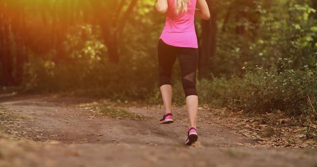 Jonge geschiktheidsvrouw die in de ochtend bospad lopen. gezond fit leven.