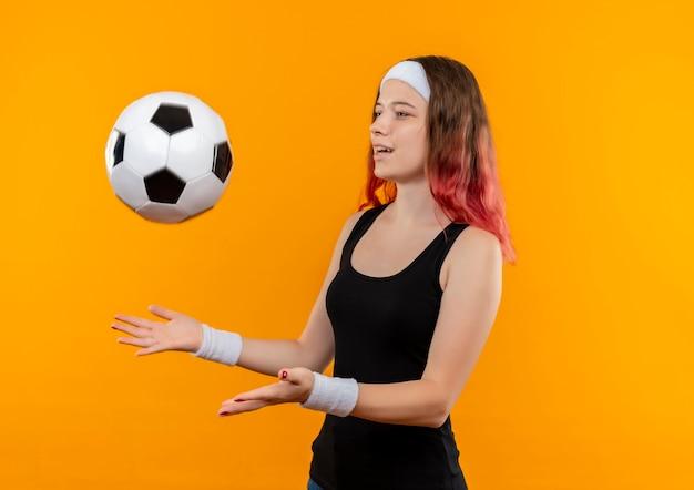 Jonge geschiktheidsvrouw die in sportkleding voetbalbal gelukkige en positieve status over oranje muur werpen