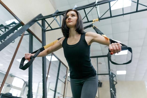 Jonge geschiktheidsvrouw die oefeningen doet die het riemensysteem gebruiken