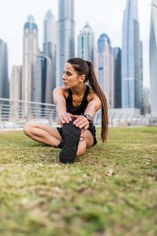 Jonge geschiktheidsvrouw het uitrekken zich benen die vóór training op wolkenkrabbersruimte opwarmen