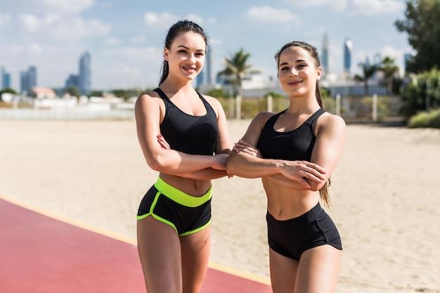 Jonge geschiktheidsvrouwen in sportwear status op het strand