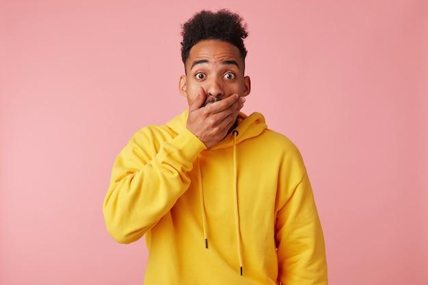 Jonge geschokt afro-amerikaanse man in gele hoodie, bedekte zijn mond met hand van verbazing