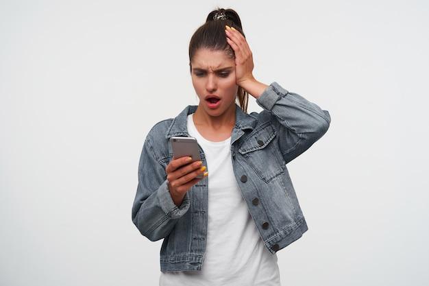 Jonge geschokt brunette dame met wijd open mond in wit t-shirt en spijkerjassen, houdt smartphone en ziet er ongelukkig uit, staat op witte achtergrond.