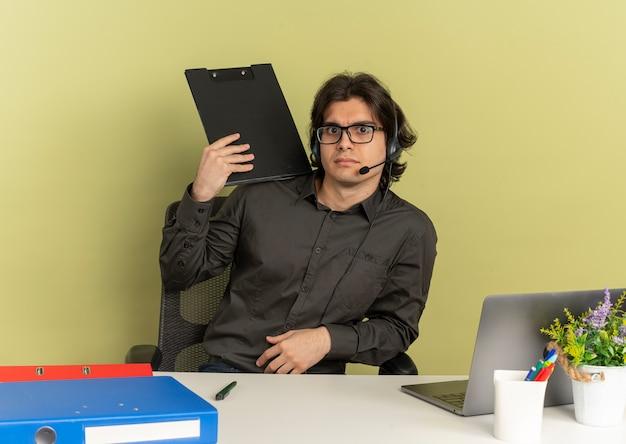 Jonge geschokt kantoor werknemer man op koptelefoon zit aan bureau houdt klembord camera kijken