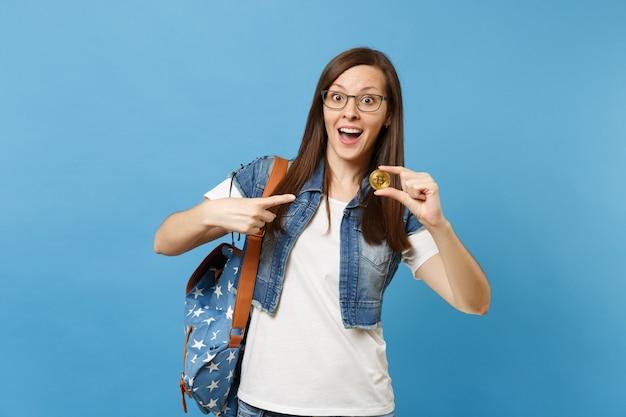 Jonge geschokt opgewonden vrouw student in glazen wijsvinger wijzend op bitcoin, metalen munt van gouden kleur geïsoleerd op blauwe achtergrond. toekomstige valuta. onderwijs in middelbare school hogeschool.
