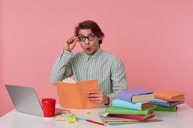 Jonge geschokt student in bril draagt in basic shirt, man zit bij de tafel en werkt met laptop, kijkt naar de camera door glazen met verbaasde uitdrukking, geïsoleerd op roze achtergrond.