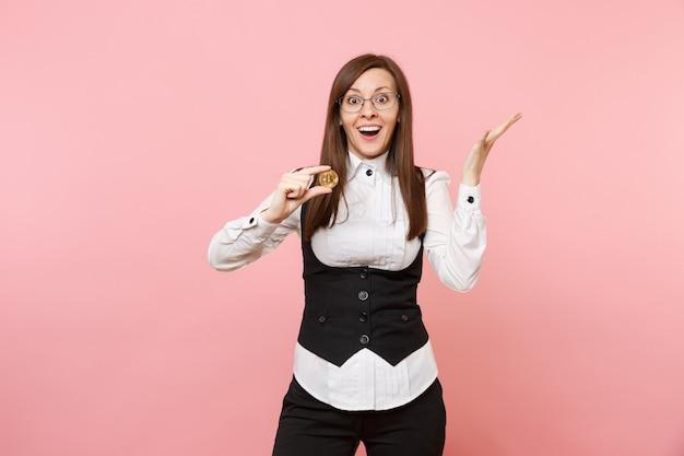 Jonge geschokt verrast zakenvrouw in glazen met bitcoin en het verspreiden van handen geïsoleerd op pastel roze achtergrond. dame baas. prestatie carrière rijkdom concept. kopieer ruimte voor advertentie.