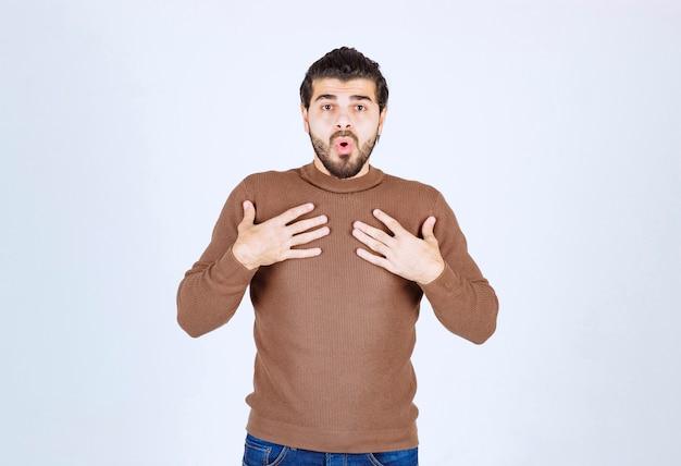 Jonge geschokte man die zijn handen op de borst zet die op een witte muur wordt geïsoleerd.
