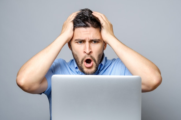 Jonge geschokte man in blauw shirt met behulp van laptop
