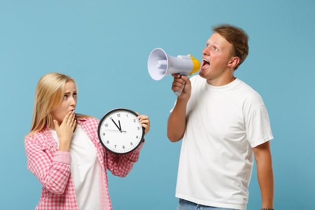Jonge geschokte paar twee vrienden, man en vrouw in wit roze lege t-shirts poseren