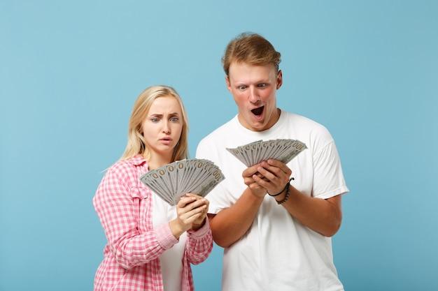 Jonge geschokte paar twee vrienden, man en vrouw in wit roze t-shirts poseren