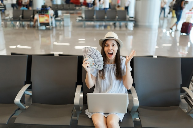 Jonge geschokte reizigerstoeristenvrouw die aan laptop werkt, houdt een bundel dollars vast, contant geld gespreide handen wachten in de lobbyhal op de luchthaven