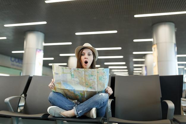 Jonge geschokte reizigerstoeristenvrouw met gekruiste benen houdt papieren kaart vast, zoekt route in lobbyhal op internationale luchthaven
