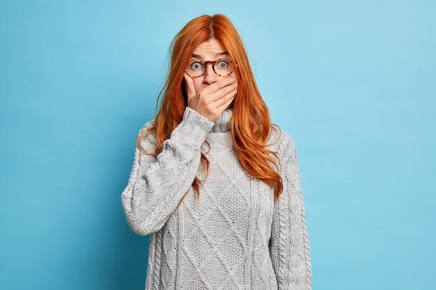 Jonge geschokte roodharige jonge vrouw bedekt mond en staart stomverbaasd hoort gênant nieuws draagt doorzichtige bril grijze gebreide trui.