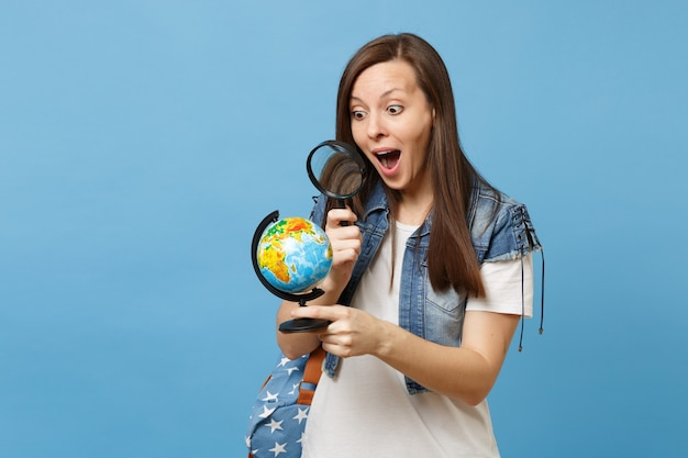 Jonge geschokte verbaasde vrouw student in denim kleding met rugzak op zoek op wereldbol met vergrootglas leren aardrijkskunde geïsoleerd op blauwe achtergrond. onderwijs in middelbare school hogeschool.