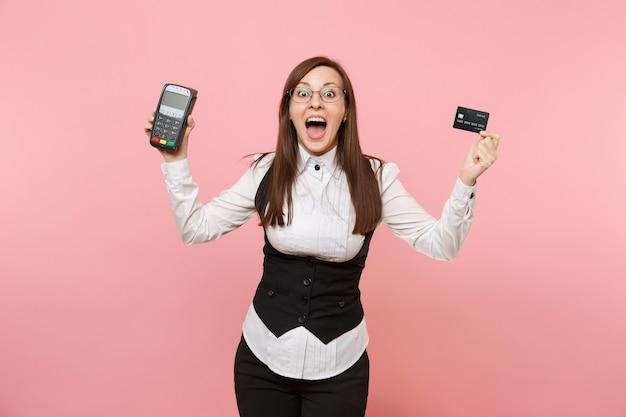Jonge geschokte verbaasde zakenvrouw houdt draadloze moderne bankbetaalterminal vast om creditcardbetalingen te verwerken en te verwerven, zwarte kaart geïsoleerd op roze achtergrond. dame baas. prestatie carrière rijkdom.