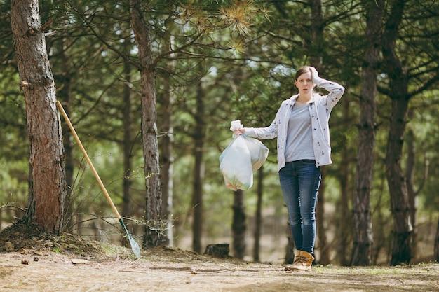 Jonge geschokte vrouw die afval schoonmaakt met vuilniszakken en zich vastklampt aan het hoofd in het park. probleem van milieuvervuiling