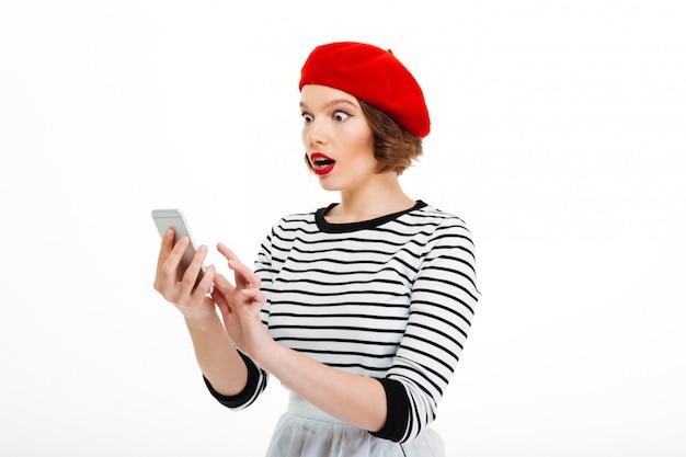 Jonge geschokte vrouw die door mobiele telefoon babbelt