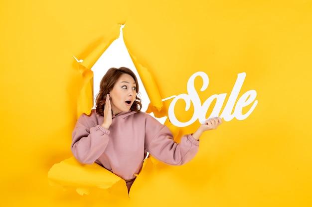 Jonge geschokte vrouw die verkoopteken op gele gescheurde doorbraakachtergrond houdt