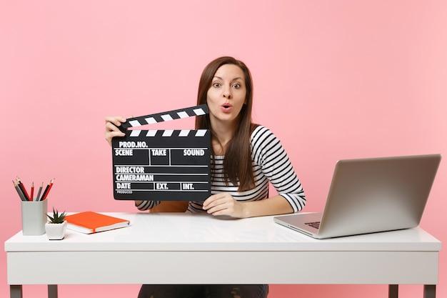 Jonge geschokte vrouw houdt klassieke zwarte film vast die filmklapper maakt terwijl ze aan een project werkt terwijl ze op kantoor zit met een laptop geïsoleerd op een pastelroze achtergrond. prestatie zakelijke carrière concept. ruimte kopiëren.