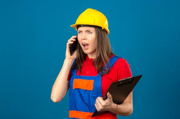 Jonge geschokte vrouw in bouw eenvormig en geel de holdingsklembord van de veiligheidshelm en het spreken door smartphone die zich op blauwe achtergrond bevinden