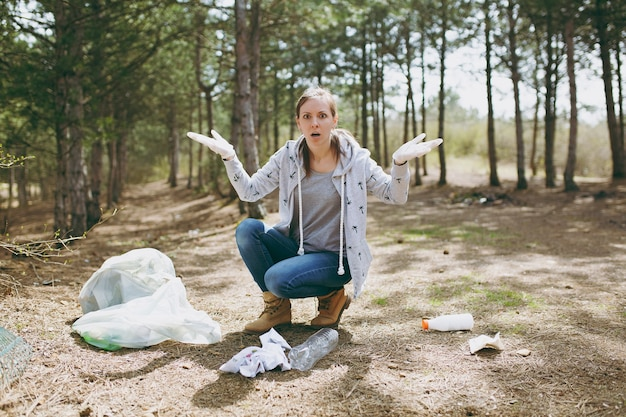 Jonge geschokte vrouw in vrijetijdskleding en handschoenen die afval schoonmaakt en handen verspreidt in de buurt van vuilniszakken in het park. probleem van milieuvervuiling