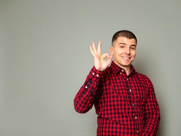 Jonge geschoren mens die ok gebaar met grote glimlach en tevreden uitdrukking toont.