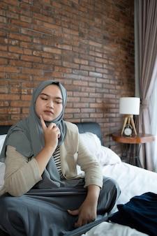 Jonge gesluierde vrouw die op het bed denkt