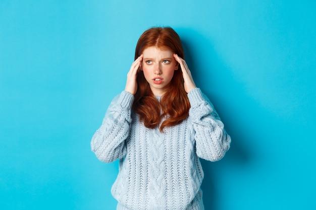 Jonge, gespannen roodharige studente probeert te denken, wrijft over de slapen en kijkt omhoog, denkt na, staat over een blauwe achtergrond