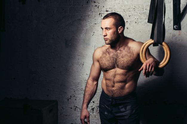 Jonge gespierde aantrekkelijke man naakte torso poseren tegen gymnastiek ringen