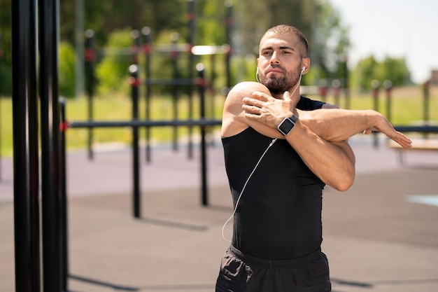 Jonge gespierde atleet in trainingspak rechterarm uitrekken tijdens het sporten