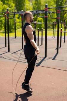 Jonge gespierde atleet in trainingspak springen met springtouw op zonnige ochtend tijdens outdoor training