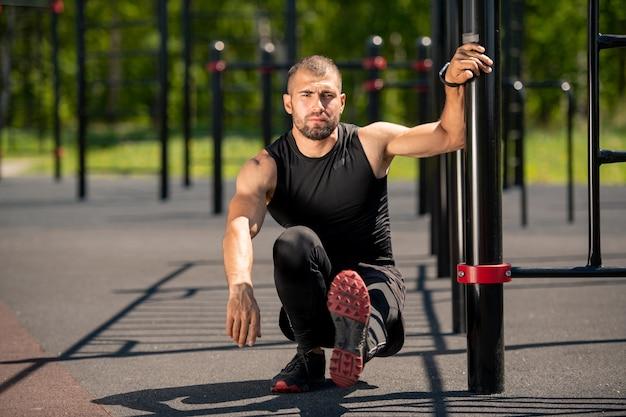 Jonge gespierde atleet zittend op kraakpanden met linkerbeen naar voren gestrekt en vasthouden door sportbar op buitensportterrein