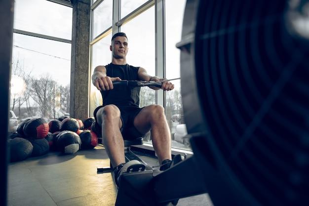 Jonge gespierde blanke atleet traint in de sportschool, doet krachtoefeningen, oefent mannelijk model werk aan zijn boven- en onderlichaam.