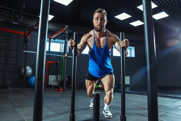 Jonge gespierde blanke atleet traint in de sportschool, doet krachtoefeningen, oefent, werkt aan zijn onderlichaam, bovenlichaam, trekt aan gewichten en halters. fitness, wellness, gezond levensstijlconcept.