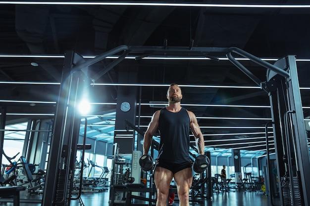 Jonge gespierde blanke atleet traint in de sportschool, doet krachtoefeningen