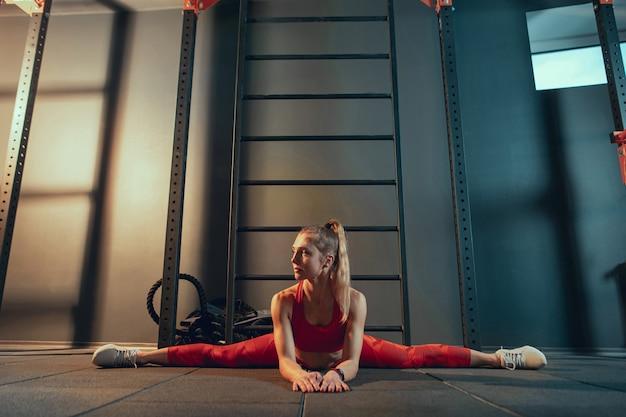 Jonge gespierde blanke vrouw oefenen in de sportschool. atletisch vrouwelijk model dat krachtoefeningen doet, haar onder-, bovenlichaam traint, zich uitstrekt.