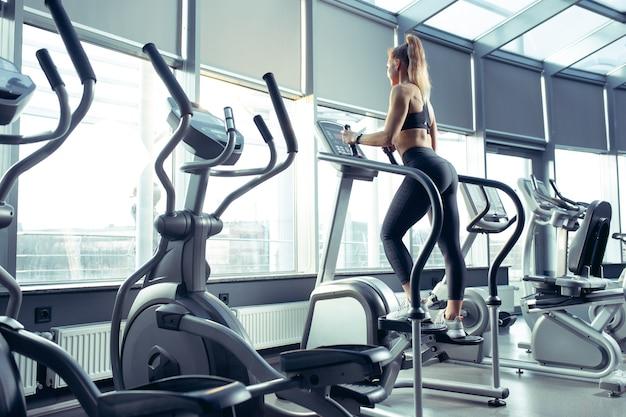 Jonge gespierde blanke vrouw oefenen in de sportschool, cardio doen. atletisch vrouwelijk model dat krachtoefeningen doet, haar bovenlichaam traint.