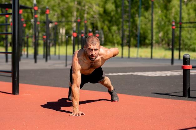 Jonge gespierde bodybuilder leunend op de voeten en de rechterhand terwijl hij de linkerarm naar achteren strekt tijdens het sporten